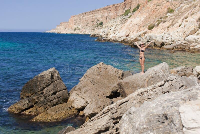 与短发被晒黑的白肤金发的妇女的海景黑比基尼泳装的 免版税库存照片