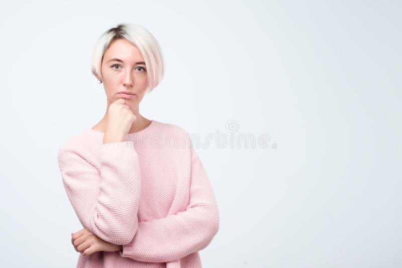 与短的被染的头发的周道的模型在站立在演播室的桃红色毛线衣穿戴了 免版税库存照片