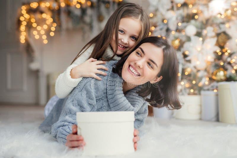 与短的黑发的愉快的女性模型和她的adorabe小女孩一起获得乐趣,庆祝圣诞节,交换礼物,有 库存图片