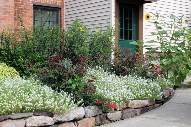 与石墙的美好的镶边石呼吁和五颜六色的花和植物 免版税库存图片