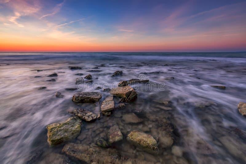 与石头的美丽的多岩石的海滩在被弄脏的水中,在日出的五颜六色的天空 免版税库存照片