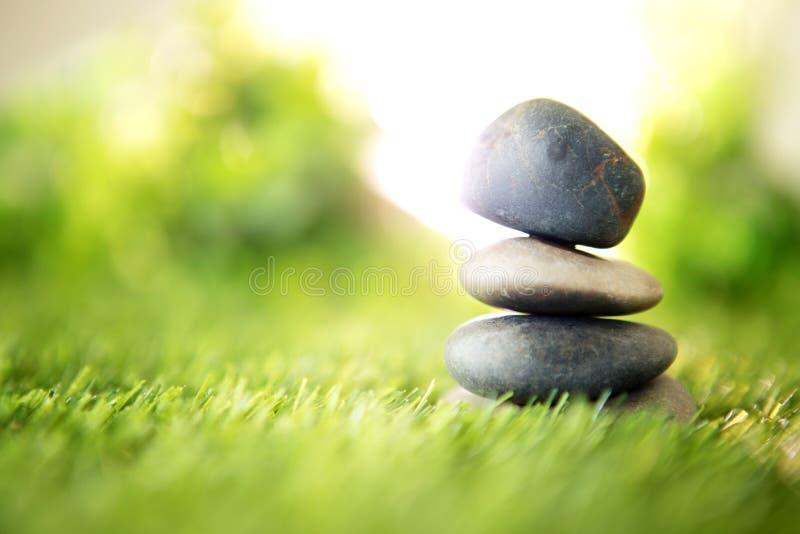 与石头金字塔的平衡在新鲜的自然绿草、温泉凝思或者福利的与禅宗概念 免版税图库摄影