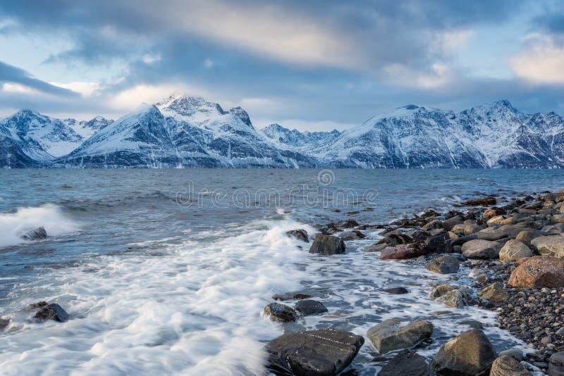 与石海滨和山的美好的冬天风景 免版税库存照片