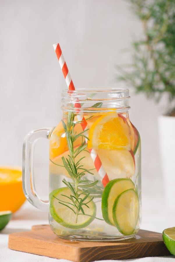 与石灰、桔子、苹果和迷迭香的被灌输的水 冷的refres 免版税图库摄影