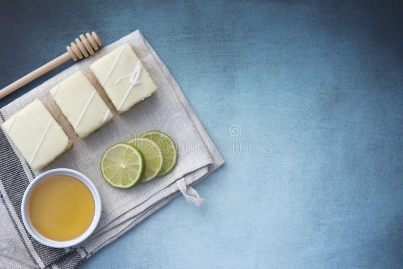 与石灰切片的三个柠檬蛋糕和一个罐蜂蜜 免版税图库摄影