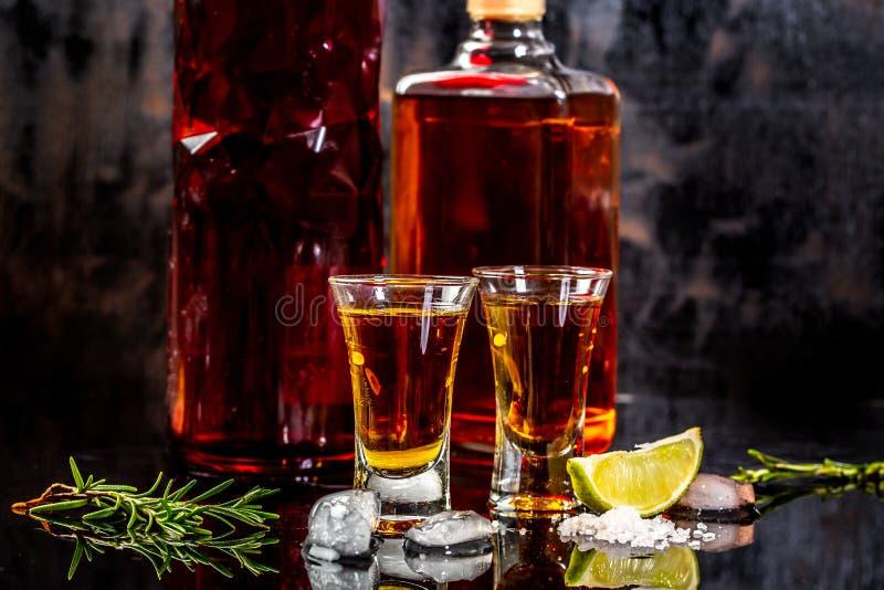 与石灰和盐的墨西哥金子龙舌兰酒在木桌,墨西哥酒精的概念上 库存照片