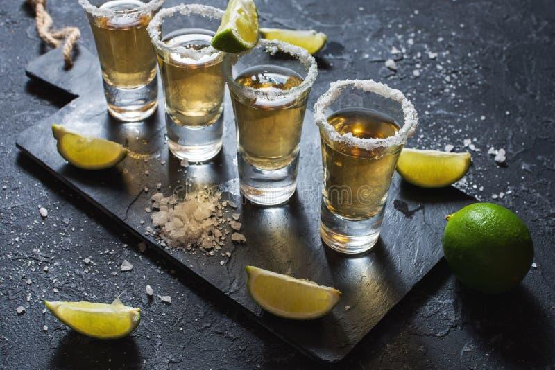 与石灰和盐的墨西哥金子龙舌兰酒在黑石背景 免版税库存图片
