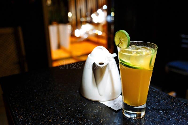 与石灰和茶壶的橙色鸡尾酒在黑暗的背景 免版税库存照片