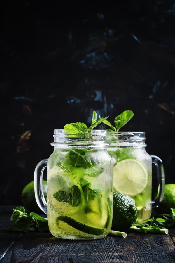 与石灰和薄菏在玻璃瓶子,黑暗的背景的被冰的绿茶 库存图片