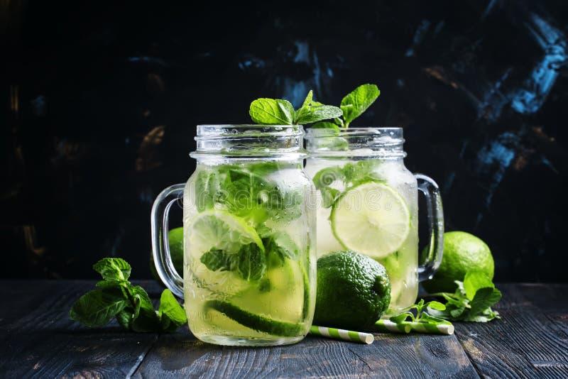 与石灰和薄菏在玻璃瓶子,黑暗的背景的被冰的绿茶 免版税库存照片