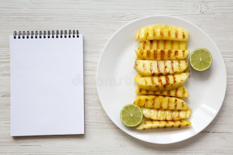 与石灰的烤菠萝切片在白色板材和空白的笔记本在白色木背景,顶视图 夏天食物 免版税库存照片