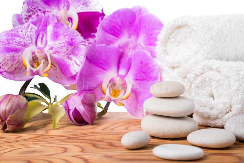 与石头、淡紫色兰花和毛巾的温泉设置被隔绝 免版税图库摄影