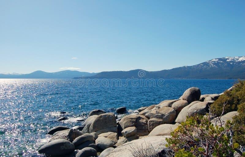 与石头和雪山的太浩湖岸 免版税库存照片