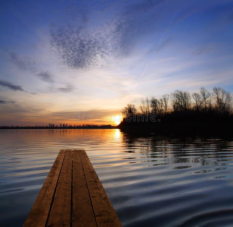 与码头和日落的河风景在河 免版税库存图片
