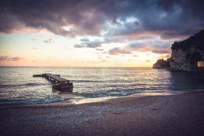 与码头的日落海滩和剧烈的梯度橙色天空和峭壁在黑山沿岸航行 免版税库存照片