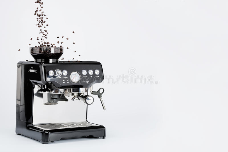 与研磨机的黑手工咖啡壶和在白色背景,侧视图的落的咖啡豆 库存照片