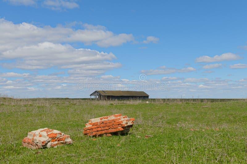 与砖墙和一个被破坏的谷仓的遗骸的一个领域 库存图片