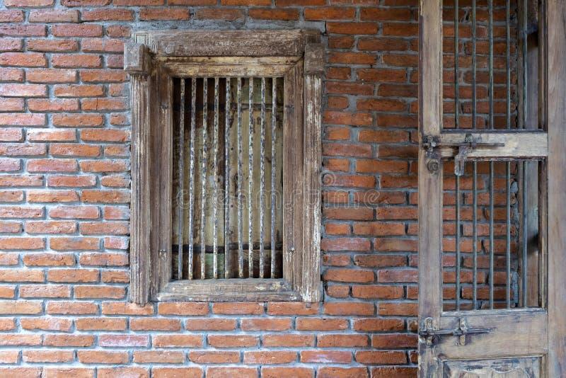 与砖墙装饰的古色古香的木窗口 免版税图库摄影