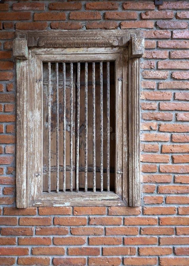 与砖墙装饰的古色古香的木窗口 免版税库存图片