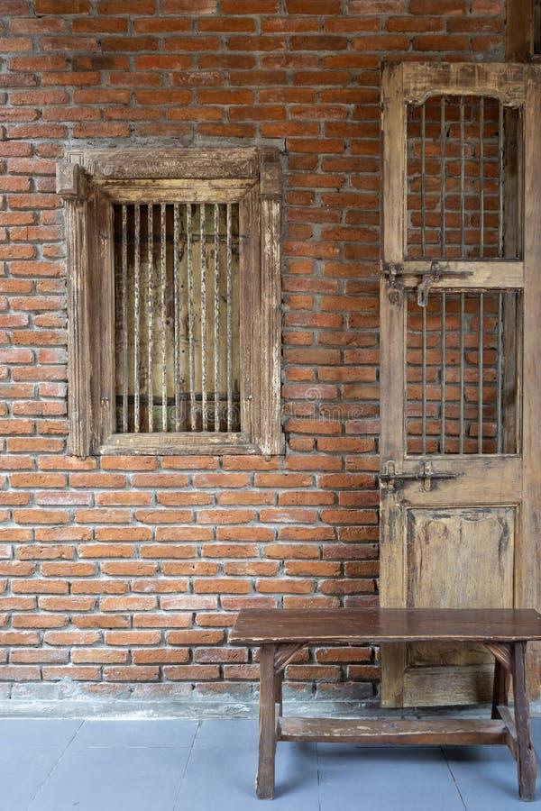 与砖墙装饰的古色古香的木窗口 库存图片