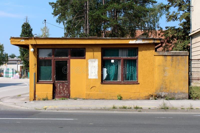 与破裂的木门和门面的被放弃的老保安大厦与树和建筑材料在背景中 免版税图库摄影