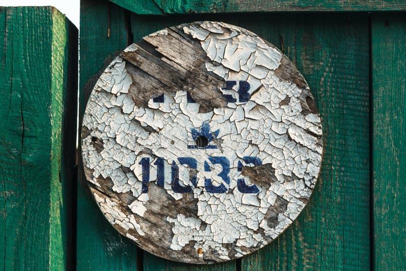 与破裂的白色油漆和被模板印刷的题字的木圈子 库存图片