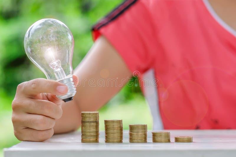 与硬币堆的电灯泡在木桌上早晨 能量和节约金钱,认为和财政概念 免版税库存图片