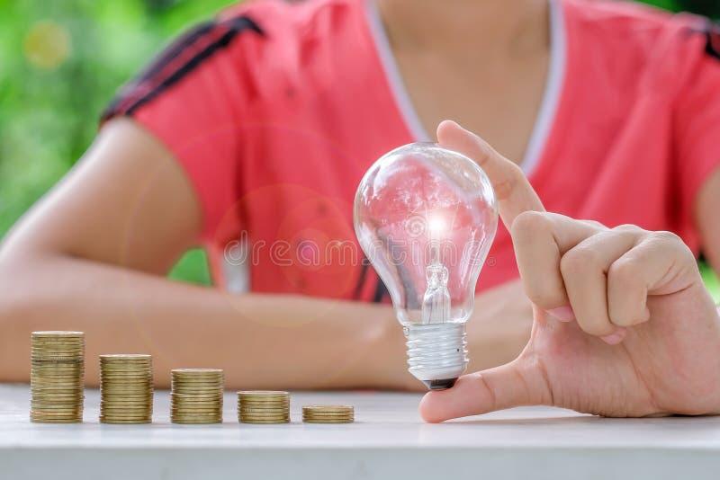 与硬币堆的电灯泡在木桌上早晨 能量和节约金钱,认为和财政概念 库存图片