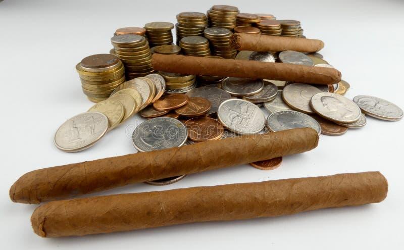 与硬币的古巴雪茄在白色 免版税库存照片