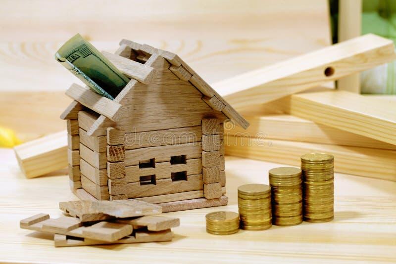与硬币的木房子块 (财务、物产和房子贷款 免版税库存照片