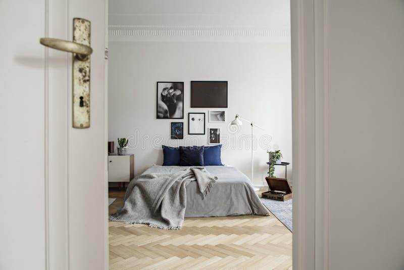 与硬木地板、美术画廊和最低纲领派装饰的宽敞和自然卧室内部 免版税库存照片