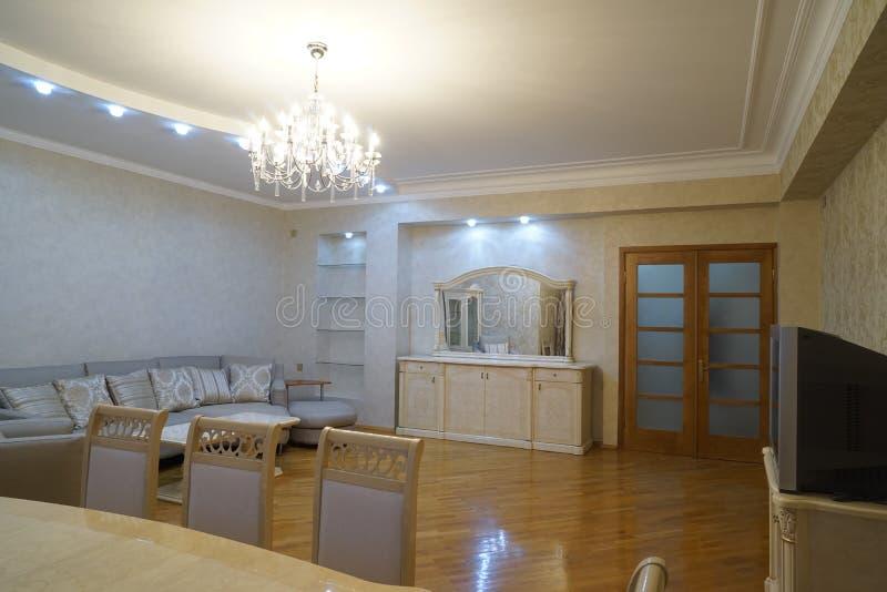 与硬木地板的美好的客厅内部和壁炉咆哮火在新的豪华家 免版税库存照片