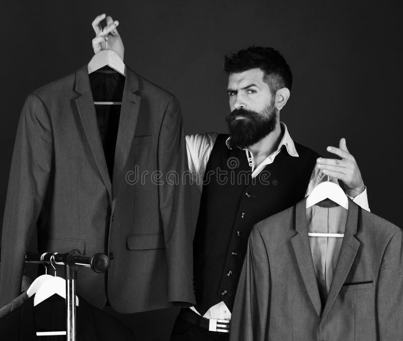 与确信的面孔的商人拿着在绿色背景的夹克 有胡子的人由衣裳机架 正式衣橱 库存图片