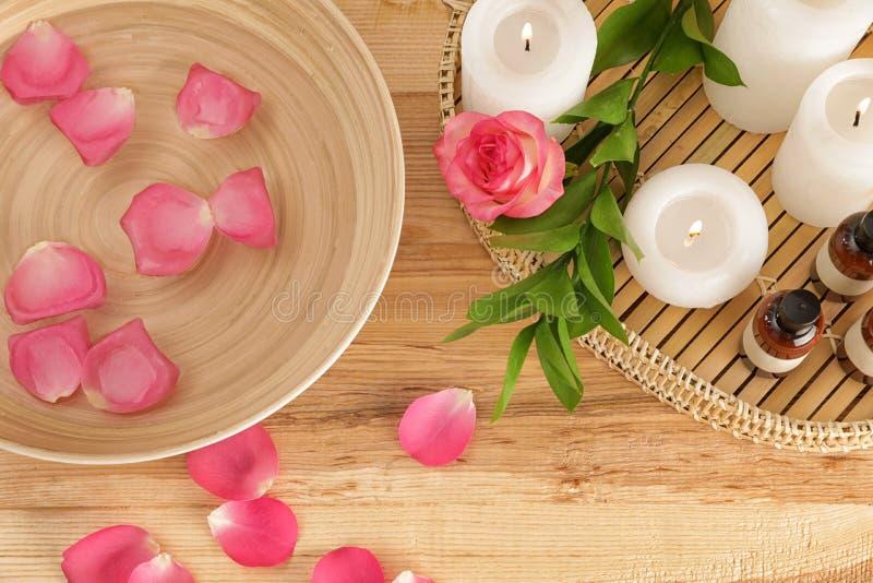 与碗的平的被放置的构成水,玫瑰花瓣和蜡烛 7?? 免版税库存图片