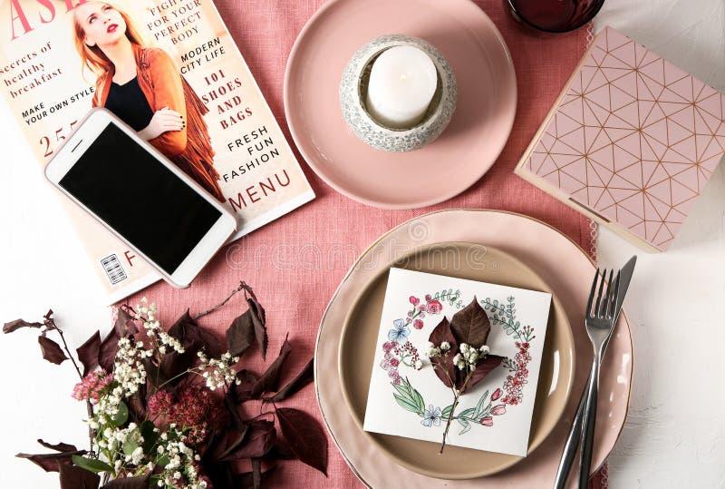 与碗筷、手机、花卉装饰和杂志的平的被放置的构成在颜色背景 免版税图库摄影