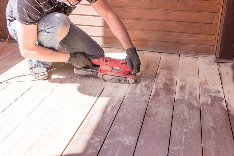 与磨床的铺沙的硬木地板 在公寓的修理,乡间别墅,露台 做木条地板的木匠 免版税库存照片
