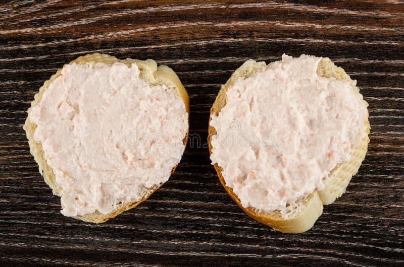 与磷虾浆糊的两个三明治在木桌上 r 免版税库存图片
