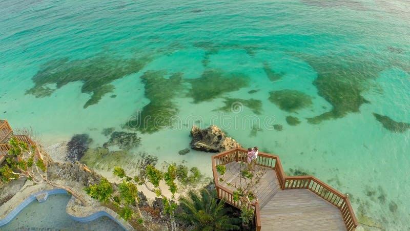 与礁石的美丽的浅绿色的海岸和在阳台的一对爱恋的夫妇在海滩上 美好的本质的 免版税库存照片