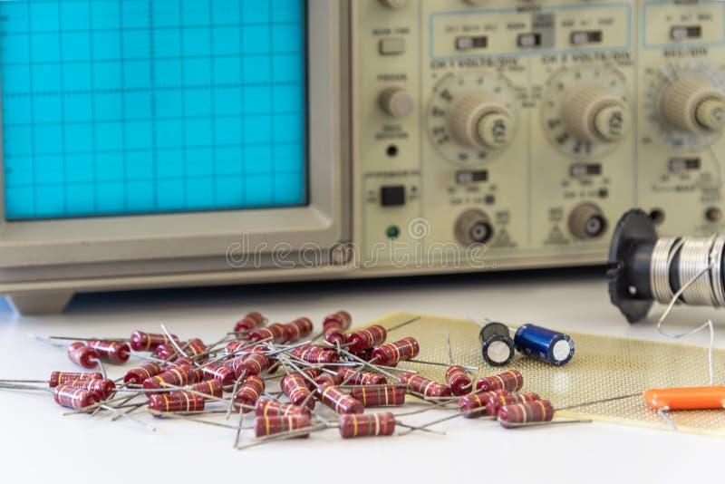 与示波器的电子元件在白色桌上 免版税库存照片