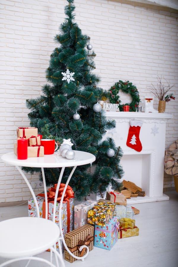 与礼物的圣诞树在一个白色砖墙的背景在壁炉附近的 免版税库存图片
