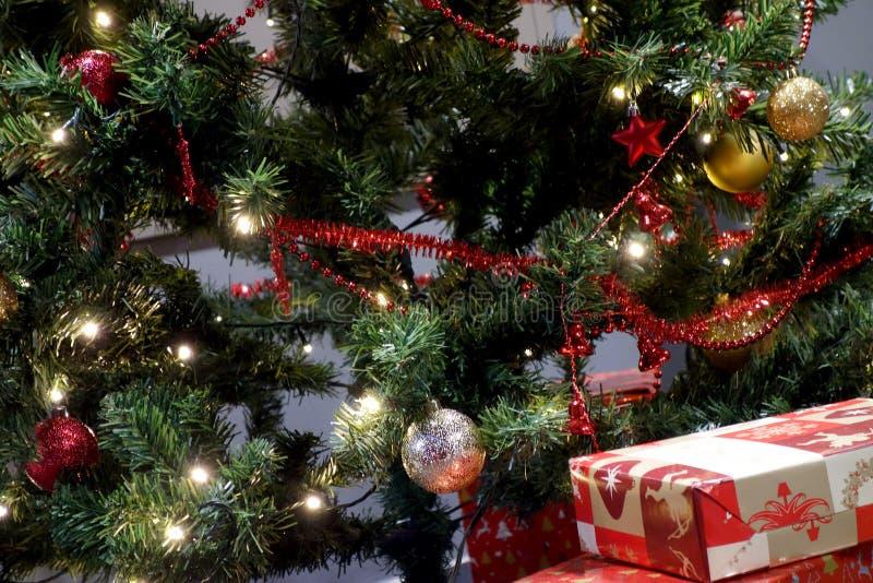 与礼物的圣诞树在温暖的夜 免版税库存照片