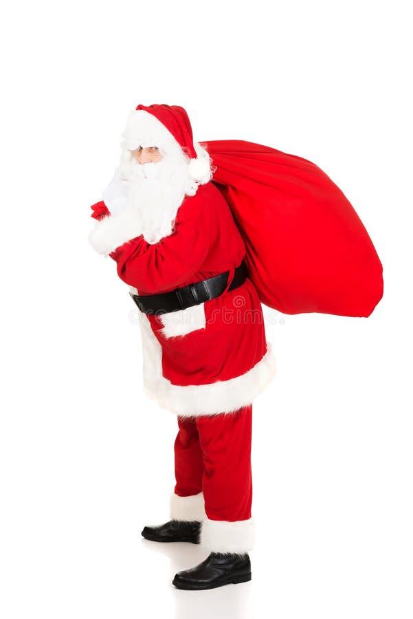 与礼物的圣诞老人运载的袋子 免版税图库摄影