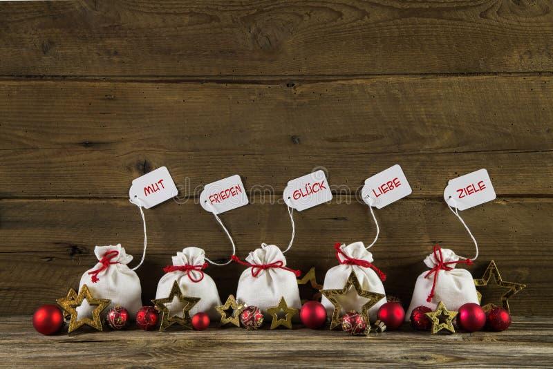 与礼物的德国圣诞节在木后面的问候和文本 图库摄影