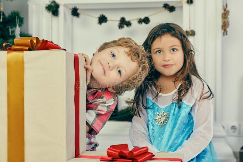 与礼物的快乐的逗人喜爱的一点childs 拿着礼物盒的男孩和女孩临近圣诞树户内 免版税库存照片