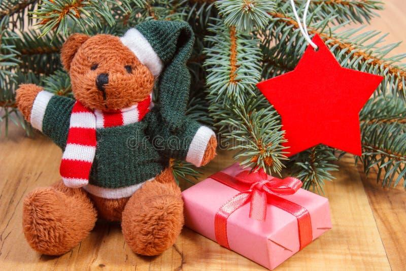与礼物的玩具熊圣诞节、云杉的分支和红色星的 免版税库存照片