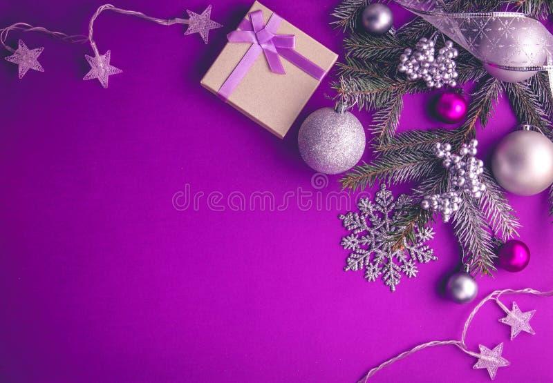 与礼物的紫色圣诞节背景 库存图片