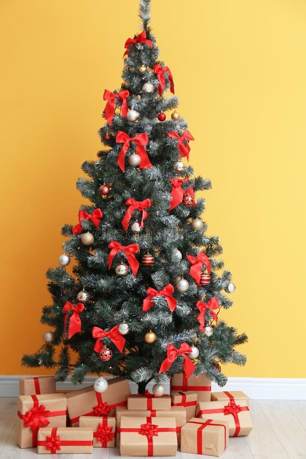 与礼物的美丽的圣诞树临近颜色墙壁 免版税库存照片