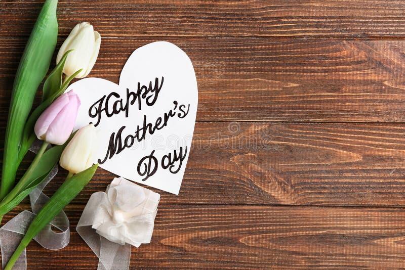 与礼物的美好的构成和手工制造卡片为在木背景的母亲节 图库摄影