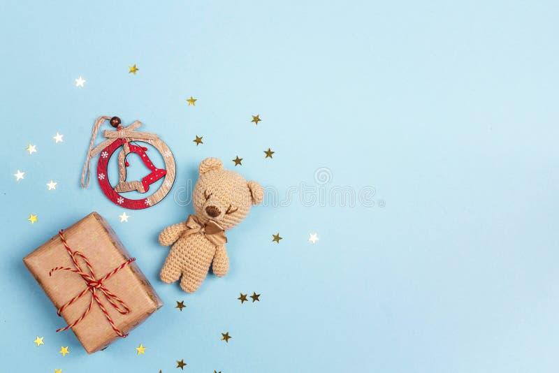 与礼物盒、响铃和玩具熊的蓝色圣诞节背景 复制 库存图片