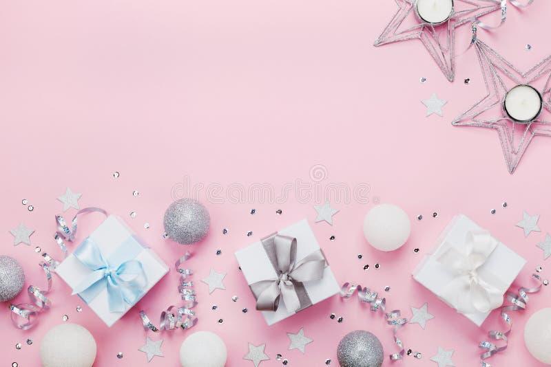 与礼物盒、球、装饰和衣服饰物之小金属片的圣诞节边界在桃红色台式视图 平的位置 复制贺卡的空间 免版税库存照片